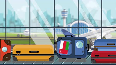 toon : Suitcases with Oman flag stickers on baggage carousel in airport, close-up. Omani tourism related loopable cartoon animation Stock Footage