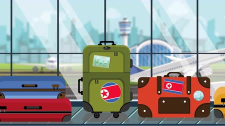 dprk : Suitcases with North Korea flag stickers on baggage carousel in airport, close-up. Tourism related loopable cartoon animation