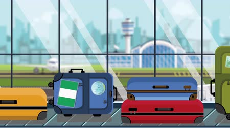 nigeria flag : Suitcases with Nigerian flag stickers on baggage carousel in airport, close-up. Travel to Nigeria related loopable cartoon animation