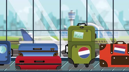istek : Baggage with Netherlands flag stickers on carousel in airport, close-up. Travel related loopable cartoon animation Stok Video