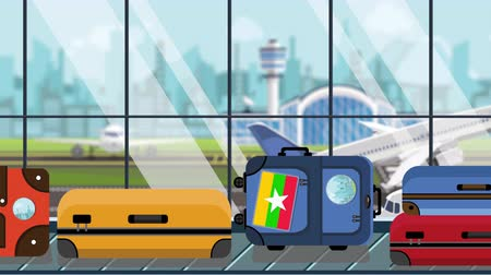 istek : Suitcases with Myanma flag stickers on baggage carousel in airport, close-up. Myanmar tourism related loopable cartoon animation Stok Video