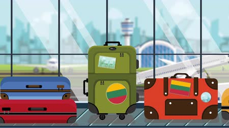 flag of lithuania : Suitcases with Lithuania flag stickers on baggage carousel in airport, close-up. Lithuanian tourism related loopable cartoon animation Stock Footage