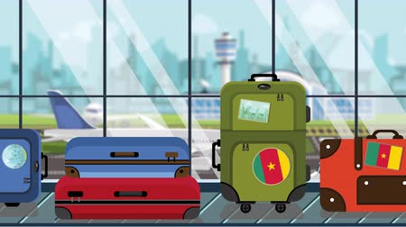 перевод : Suitcases with Cameroonian flag stickers on baggage carousel in airport, close-up. Travel to Cameroon related loopable cartoon animation