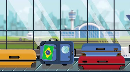 istek : Luggage with Brazil flag stickers on baggage carousel in airport, close-up. Brazilian tourism related loopable cartoon animation