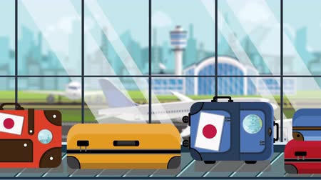 istek : Baggage with Japanese flag stickers on carousel in airport, close-up. Travel to Japan related loopable cartoon animation