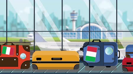 arrive : Suitcases with Italian flag stickers on baggage carousel in airport, close-up. Tourism in Italy related loopable cartoon animation