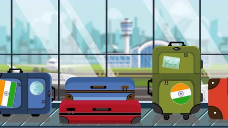 toon : Suitcases with Indian flag stickers on baggage carousel in airport, close-up. Tourism in India related loopable cartoon animation