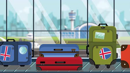 arrive : Suitcases with Iceland flag stickers on baggage carousel in airport, close-up. Icelandic tourism related loopable cartoon animation