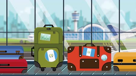 toon : Suitcases with Guatemala flag stickers on baggage carousel in airport, close-up. Guatemalan tourism related loopable cartoon animation Stock Footage