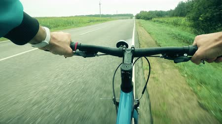 bracciale : FPV shot. Man rides a bicycle along empty road Filmati Stock