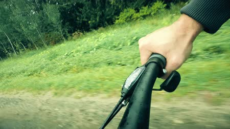 endure : Hand on a bicycle grip while riding along forest road
