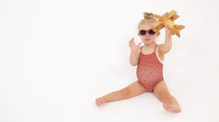 genérico : Baby girl wearing swimsuit and sunglasses plays with generic wooden plane. Vacation related clip