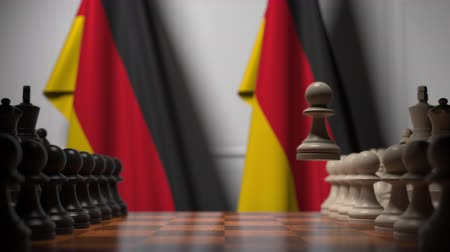 oposição : Flags of Germany behind chess board. The first pawn moves in the beginning of the game. Political rivalry conceptual 3D animation