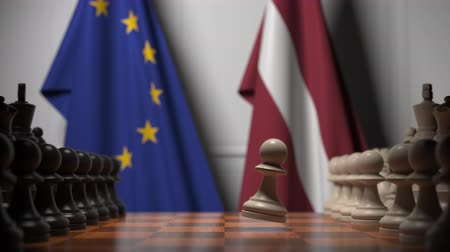 라트비아 : Flags of the EU and Latvia behind chess board. The first pawn moves in the beginning of the game. Political rivalry conceptual 3D animation 무비클립
