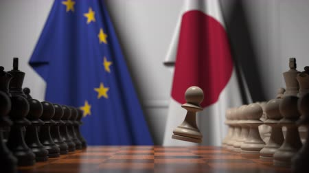 pieza de ajedrez : Flags of the EU and Japan behind chess board. The first pawn moves in the beginning of the game. Political rivalry conceptual 3D animation
