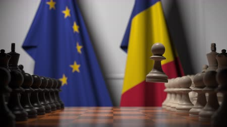 oposto : Flags of the EU and Romania behind chess board. The first pawn moves in the beginning of the game. Political rivalry conceptual 3D animation
