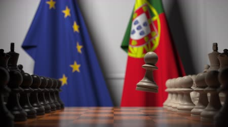 pieza de ajedrez : Flags of the EU and Portugal behind chess board. The first pawn moves in the beginning of the game. Political rivalry conceptual 3D animation Archivo de Video