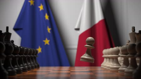 versengés : Flags of the EU and Malta behind chess board. The first pawn moves in the beginning of the game. Political rivalry conceptual 3D animation Stock mozgókép