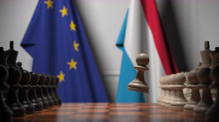 pieza de ajedrez : Flags of the EU and Luxembourg behind chess board. The first pawn moves in the beginning of the game. Political rivalry conceptual 3D animation Archivo de Video