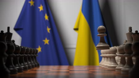 pieza de ajedrez : Flags of the EU and Ukraine behind chess board. The first pawn moves in the beginning of the game. Political rivalry conceptual 3D animation