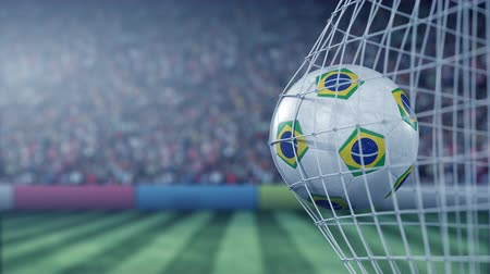 brazil : Flag of Brazil on the football hitting goal net back. Realistic slow motion 3D animation