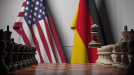 pedina : Flags of United States and Germany behind chess board. The first pawn moves in the beginning of the game. Political rivalry conceptual 3D animation