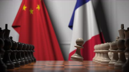 oposto : Flags of China and France behind chess board. The first pawn moves in the beginning of the game. Political rivalry conceptual 3D animation