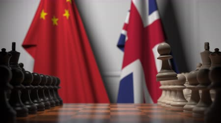 pieza de ajedrez : Flags of China and the UK behind chess board. The first pawn moves in the beginning of the game. Political rivalry conceptual 3D animation