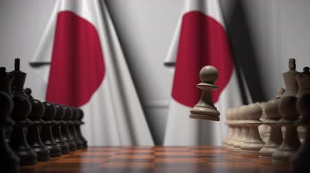 pedina : Flags of Japan behind chess board. The first pawn moves in the beginning of the game. Political rivalry conceptual 3D animation