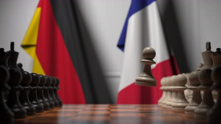 pieza de ajedrez : Flags of Germany and France behind chess board. The first pawn moves in the beginning of the game. Political rivalry conceptual 3D animation