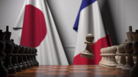 oposição : Flags of Japan and France behind chess board. The first pawn moves in the beginning of the game. Political rivalry conceptual 3D animation