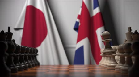 oposto : Flags of Japan and Great Britain behind chess board. The first pawn moves in the beginning of the game. Political rivalry conceptual 3D animation