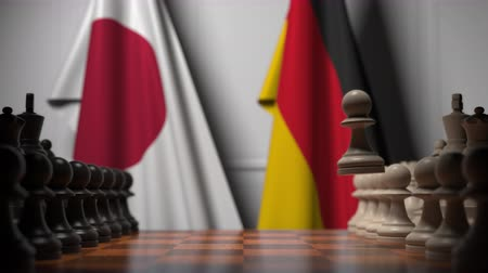 estratégico : Flags of Japan and Germany behind chess board. The first pawn moves in the beginning of the game. Political rivalry conceptual 3D animation