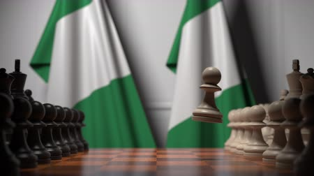 nigeria flag : Flags of Nigeria behind pawns on the chessboard. Chess game or political rivalry related 3D animation Stock Footage