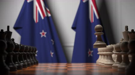 nowa zelandia : Flags of New Zealand behind pawns on the chessboard. Chess game or political rivalry related 3D animation