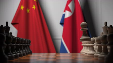 dprk : Flags of China and North Korea behind pawns on the chessboard. Chess game or political rivalry related 3D animation