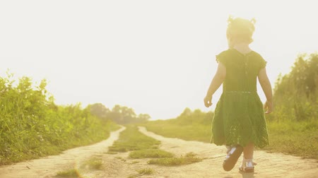 szandál : Steadicam shot of baby girl walking along rural field pathway on a sunny summer evening