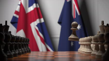 treaty : Chess game against flags of Great Britain and Australia. Political competition related 3D animation Stock Footage
