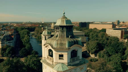 немецкий : Aerial orbiting shot of the tower of historic Mullersches Volksbad public bath in cityscape of Munich, Germany