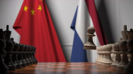 satranç tahtası : Chess game against flags of China and Netherlands. Political competition related 3D animation Stok Video