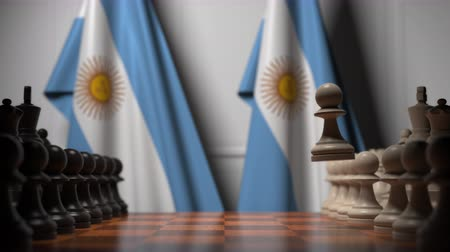 ライバル : Flags of Argentina behind pawns on the chessboard. Chess game or political rivalry related 3D animation