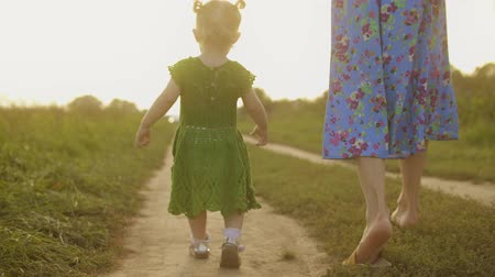 szandál : Baby girl in green dress and her mum walk along rural field pathway together on a sunny summer evening