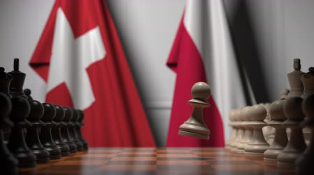 конкурировать : Flags of Switzerland and Poland behind pawns on the chessboard. Chess game or political rivalry related 3D animation Стоковые видеозаписи