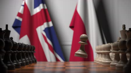 конкурировать : Flags of Britain and Poland behind pawns on the chessboard. Chess game or political rivalry related 3D animation