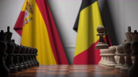 belga : Flags of Spain and Belgium behind pawns on the chessboard. Chess game or political rivalry related 3D animation