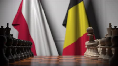 treaty : Flags of Poland and Belgium behind pawns on the chessboard. Chess game or political rivalry related 3D animation Stock Footage