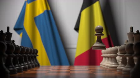 İsveççe : Flags of Sweden and Belgium behind pawns on the chessboard. Chess game or political rivalry related 3D animation Stok Video