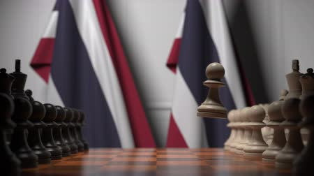 соперничество : Flags of Thailand behind pawns on the chessboard. Chess game or political rivalry related 3D animation