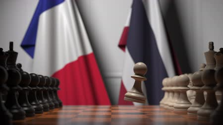 конкурировать : Flags of France and Thailand behind pawns on the chessboard. Chess game or political rivalry related 3D animation