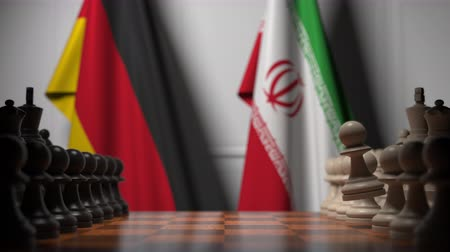 Иран : Flags of Germany and Iran behind pawns on the chessboard. Chess game or political rivalry related 3D animation